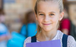 Portrait of smiling cute girl student holding book and looking at camera. Happy satisfied child wearing backpack at elementary school. Closeup face of blonde schoolgirl with school in background.