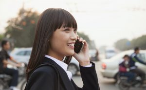 Young businesswoman using the phone outside on the street in Beijing